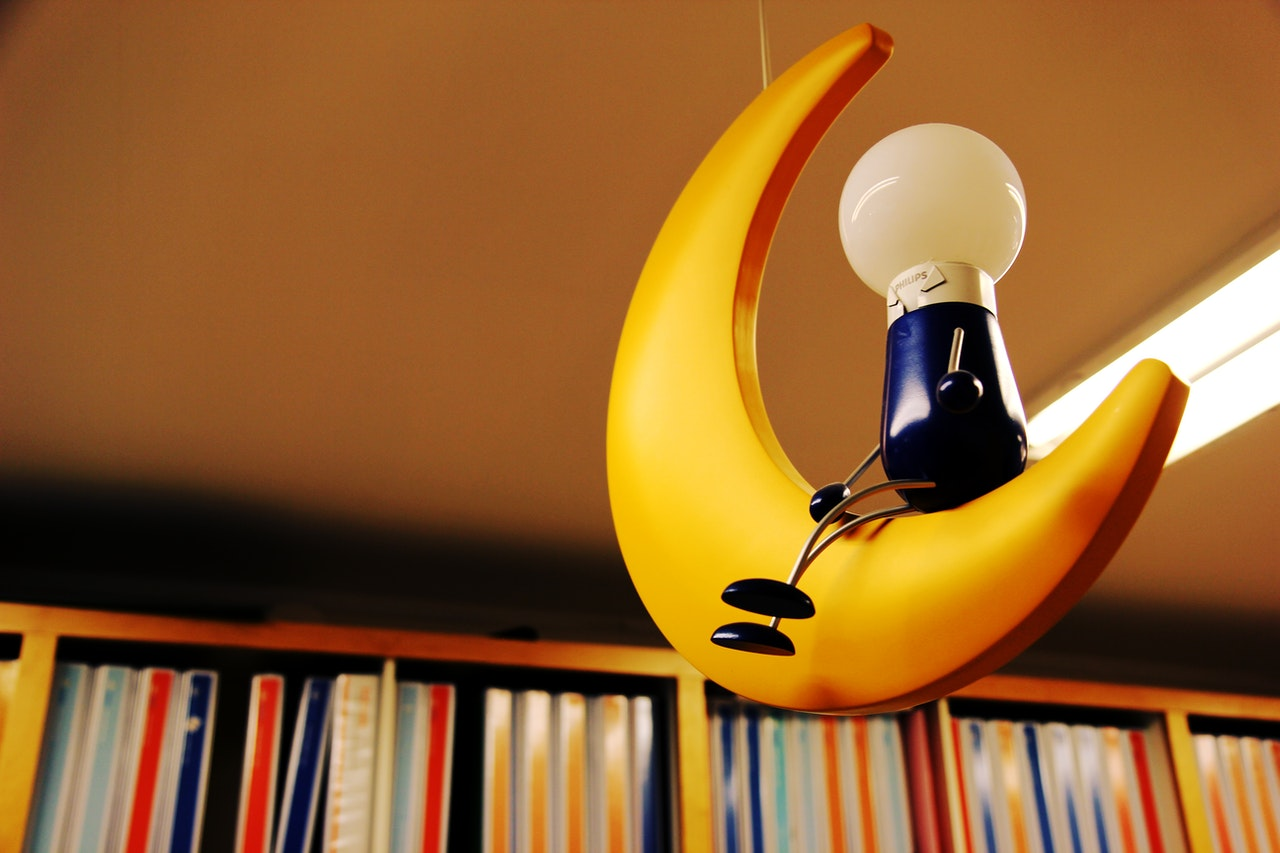 Figure sitting on plastic crescent moon with library books